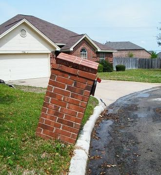 Image of a leaning brick mailbox suffering from an inadequate foundation.