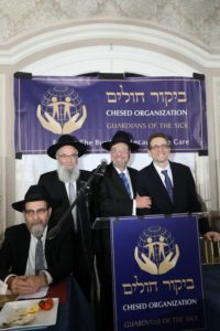 Dr. David Lefkowitz, Director of Bikur Cholim's Family Crisis Intervention Program, accepting the Ahavas Yisroel Award. (L-R) R' Yisroel Herskovits, R' Avi Fishof, Dr. David Lefkowitz