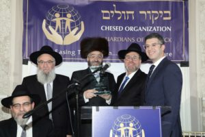 Mr. Ushi Klein accepting the Nezer Hachesed Award. (l-R) R' Yisroel Herskovits, Ushi Klein, R' Avi Fishof, Mr. Yossi Klein