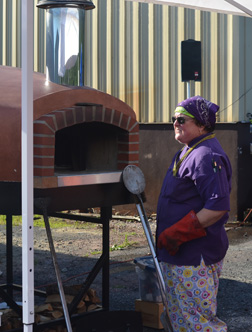 Nancy McPherson at Nancy's Air Field Café's outdoor brick pizza oven.    Jeff Needle photo