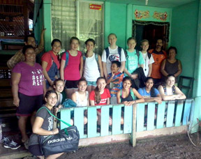 Stow's Katherine Hamilton (front row, fourth from left in red t-shirt) with the Girl Scout group and their host family at their small village home in Costa Rica.  Courtesy photo.
