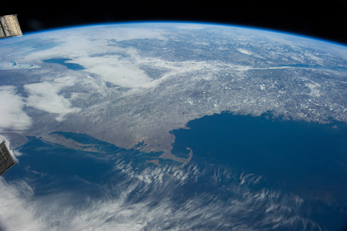 "For those based in New England, the photo above is ""our neck of the woods.""  In this winter photograph, snow blankets much of the land. The familiar hook of Cape Cod juts into the deep blue waters of the Atlantic Ocean. In the middle left, Lake Ontario peeks out under a layer of clouds, and Lake Erie is covered by ice. (Why is only one lake frozen?)   Courtesy Dan Barstow"