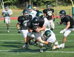 Nashoba defense takes down a Longmeadow player during last week's scrimmage.  Stow's Ben Hurley (#81) is seen at left. Nashoba's season opener is at Westborough on Saturday, September 13.                    Adrian Flatgard; frequentflyerphotographer@gmail.com