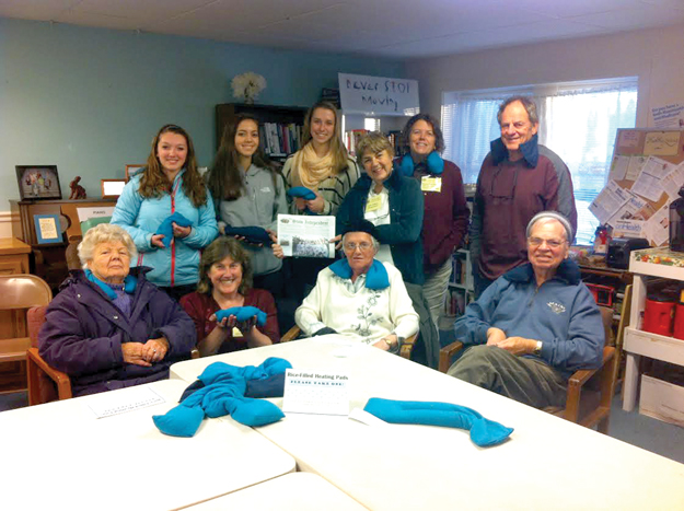 Stow Senior Girl Scout Troop 72526 donated 17 handmade rice-filled heating pads to the seniors at the COA.  Pictured (back row; left to right) are: Margo Coppes, Maria Guerin, Jordan Bricknell, Lisa Dubois (holding the Stow Independent paper), Sharon Funkhouser (COA Outreach Coordinator), Larry Weiss. Front row (l-r):  Gladys McClellan, Alyson Toole (COA Director), Ruth Banfield, & Ralph Banfield. Other troop members who helped make these:  Melissa Buck, Amanda Suleski