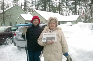 """Diane Bachtell (left) and Violet Gray stop to pose for a photo while cleaning up the snow in the Plantation Apartments parking lot after a blizzard dumped 32"""" of snow."""