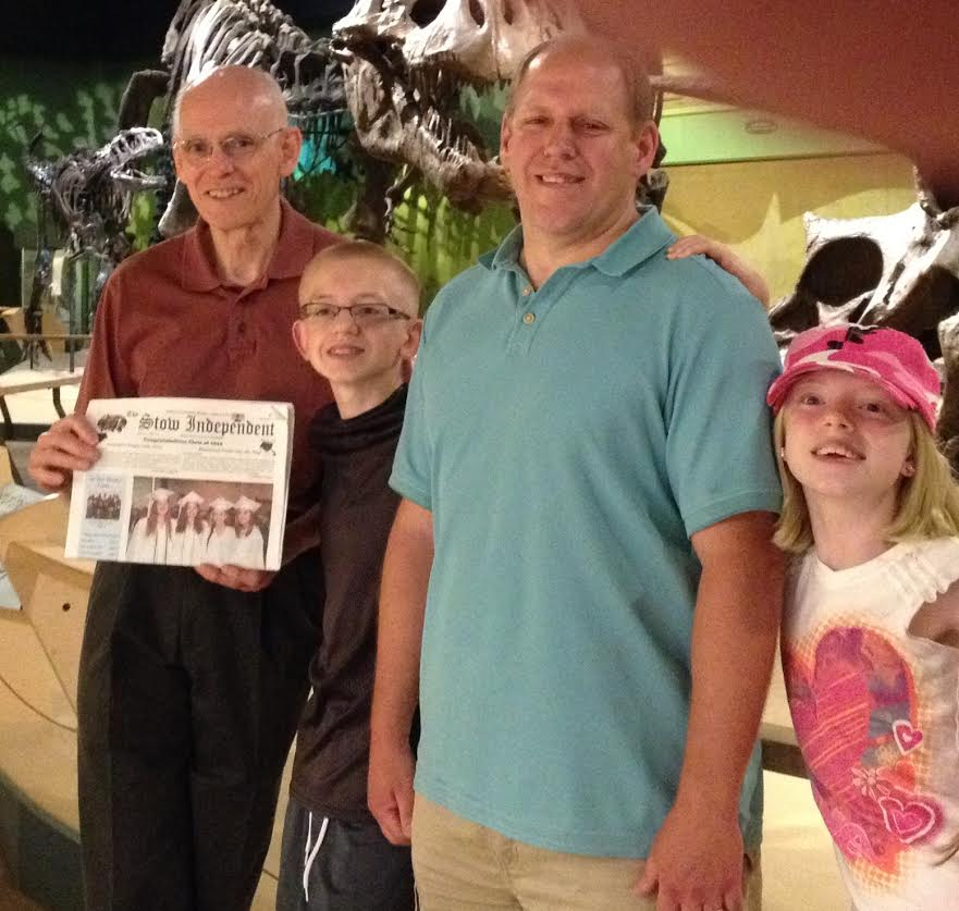 Dave Weber of Stow holding the Stow Independent while visiting the Cleveland Ohio Natural History Museum with nephew Charlie Weber and Charlie's children, Jacob and Lauren
