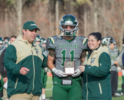 Named Defensive MVP in the Thanksgiving Day game, Egan Bachtell received his award from Coach Jamie Tucker and Athletic Director Tania Rich.             SusanShaye.com