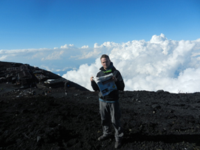 Frank Smith is reading up on current events while taking in the views from the top of Mt. Fuji in Japan