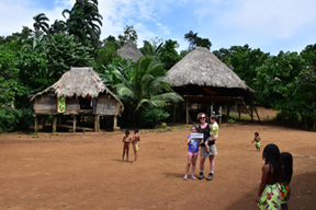 "Millie Bowler, Betsy Foley, and Nathan Bowler (photo by David Bowler) in the main area in an Embera tribal village near Alajuela Lake in Panama. Betsy wrote, ""Since there are no roads in the area, we rode in a motorized dugout canoe for about 45 min to get there.  We were treated to traditional music and dance, a fried fish and plantain lunch with fresh fruit for dessert, and lessons on medicinal plants and how the local handicrafts are made.  It was an eye opening and educational experience!"""