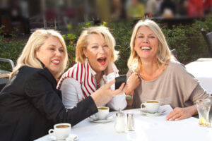 Three Ladies Sharing Laughs and Drinking Coffee Outside