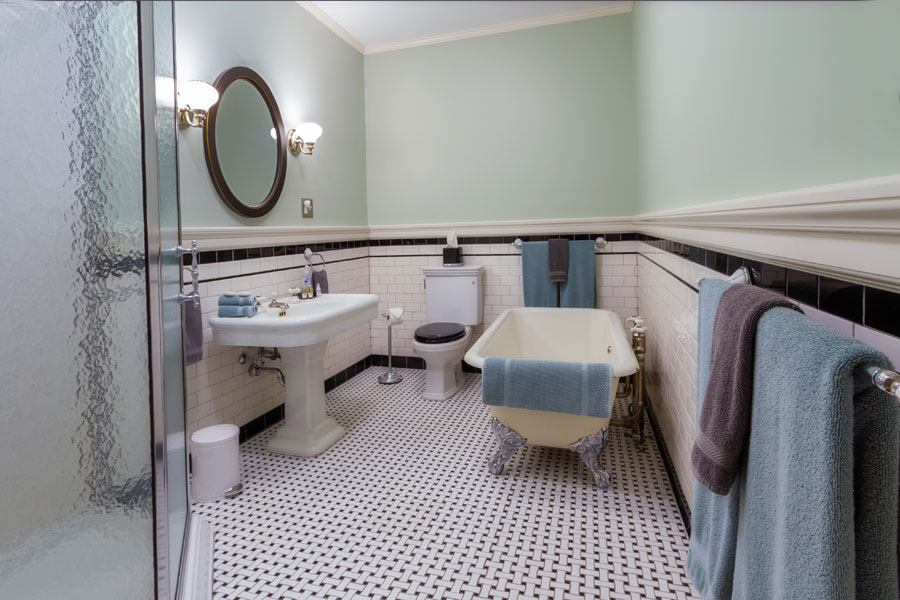 gunston guestroom bathroom with shower pedestal sink and clawfoot tub at the inn at forest oaks in natural bridge virginia