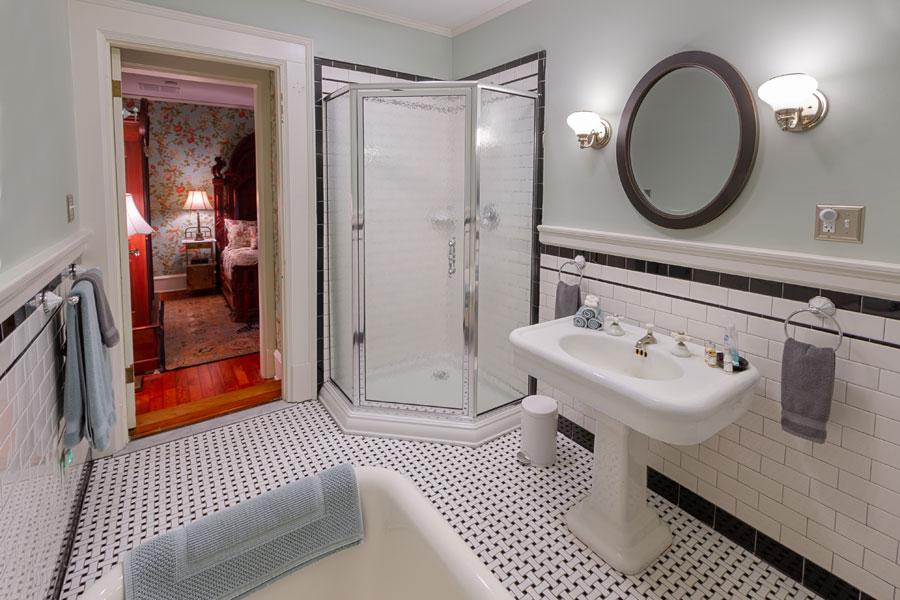 gunston guestroom bathroom with shower pedestal sink and oval mirror at the inn at forest oaks in natural bridge virginia