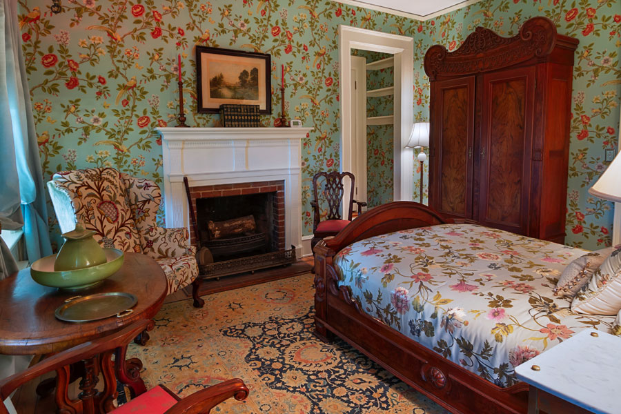 gunston guestroom with wood bed antique wardrobe and fireplace at the inn at forest oaks in natural bridge virginia