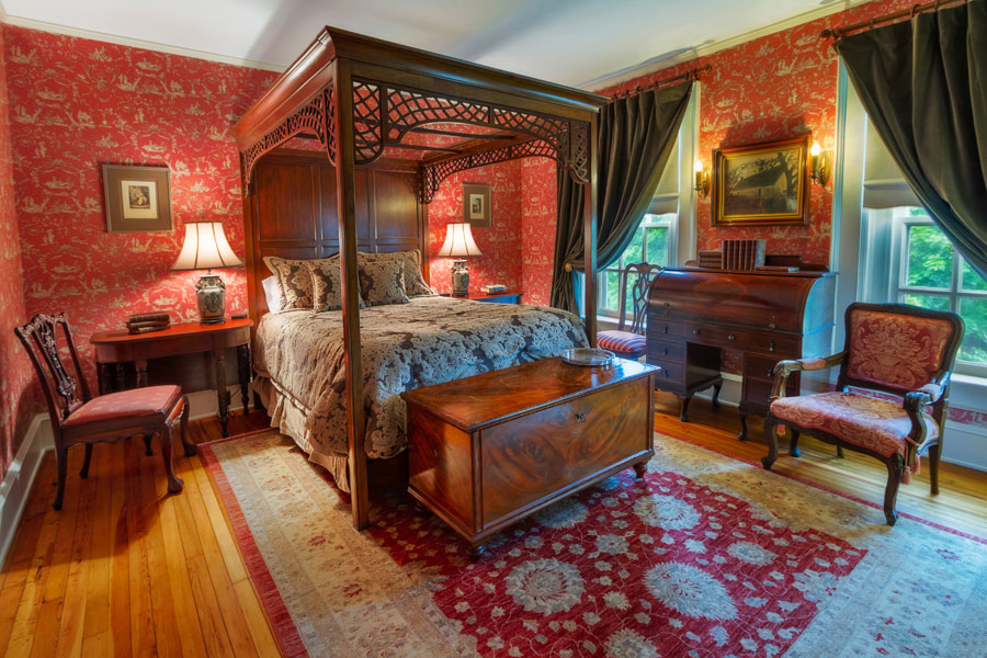 long branch guestroom with ornate antique queen bed and decor at the inn at forest oaks