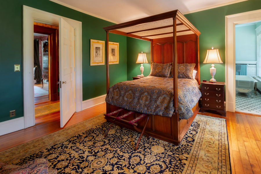 milburne room antique bed wood floors and green walls at the inn at forest oaks in natural bridge virginia