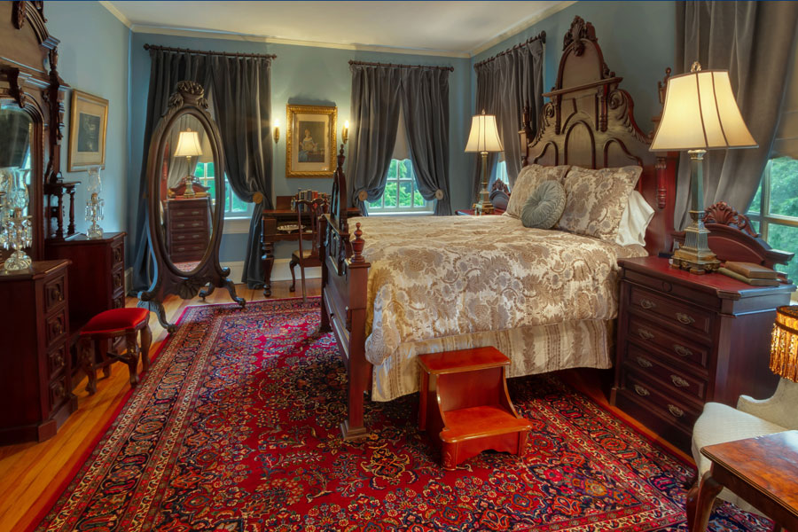 oatlands bedroom with ornate rug antique furniture and queen bed at the inn at forest oaks in natural bridge virginia