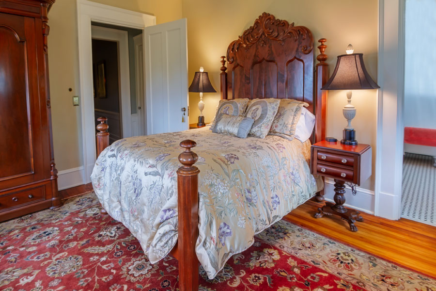 shirley guestroom antique wood bed with nightstand at the inn at forest oaks in natural bridge virginia