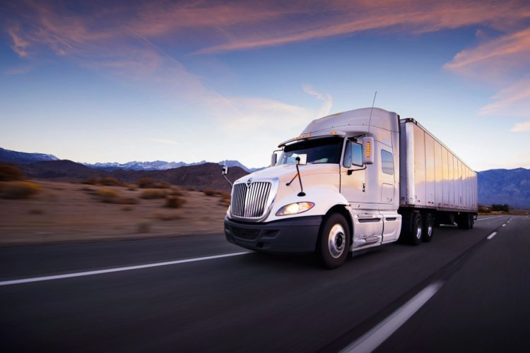 Image of a semi truck traveling along a road at sunset.