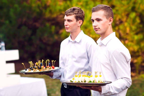 Two Servers holding trays of delicious appetizers.