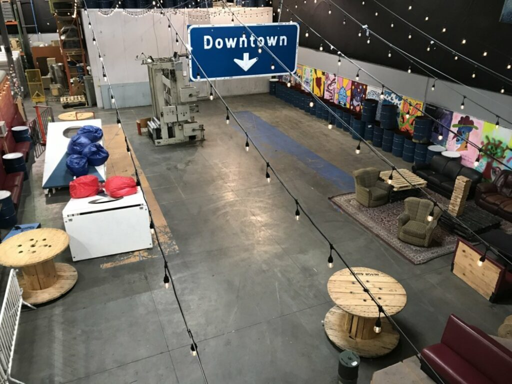 view of the brewery with giant cornhole and various seating arrangements