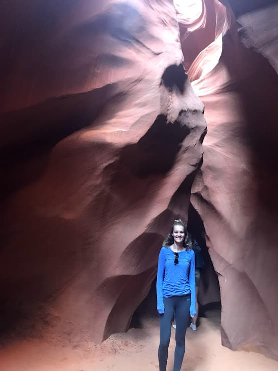 the walls of Antelope Canyon forming a face with a woman (me) standing underneath