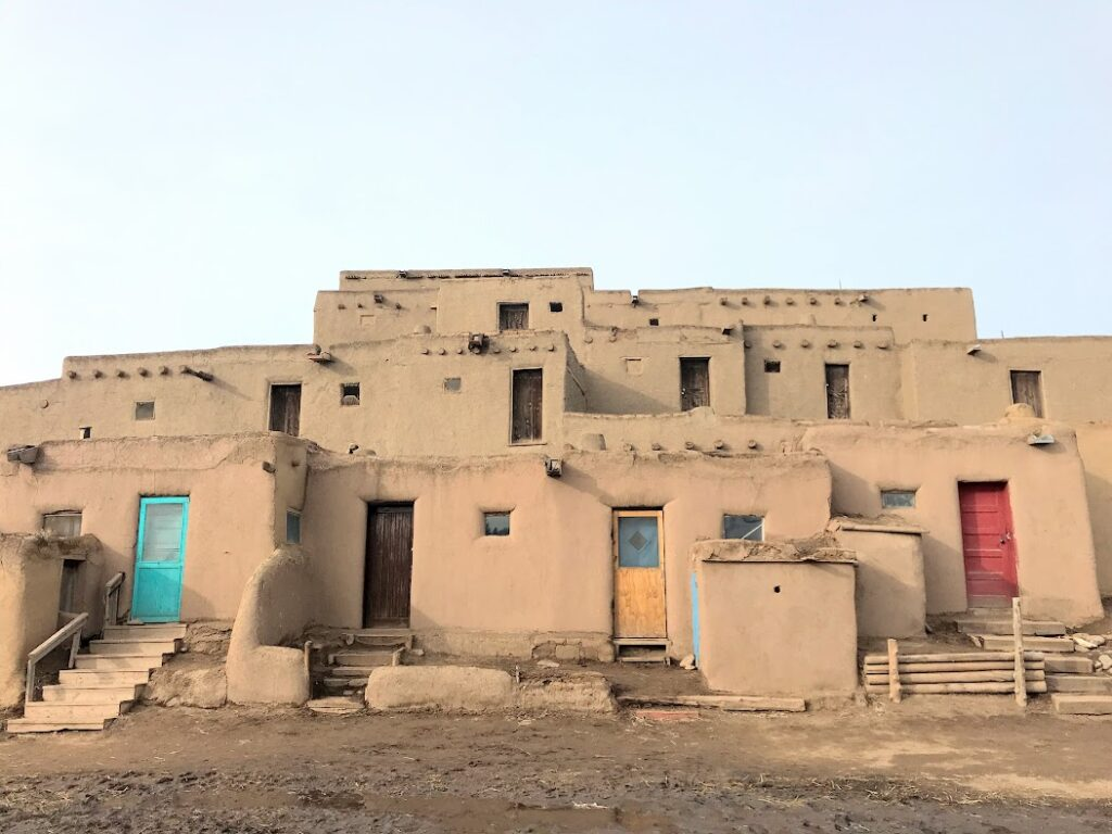 A 5 story structure of adobe buildings with brightly colored doors