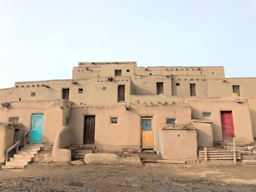 A group of multistoried pueblo style brown buildings with brightly colored doors against a blue sky