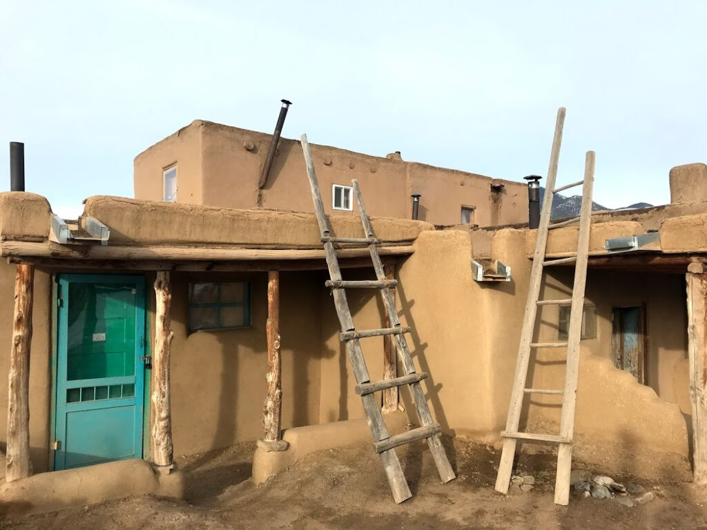 A two story adobe building with a turquoise door and wooden ladders leaning against it.