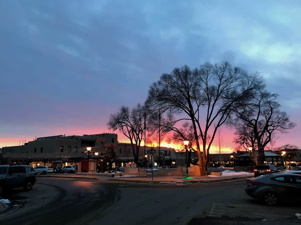 a pink and purple sunset behind the silhouette of a tree in the dimly lit plaza of Taos