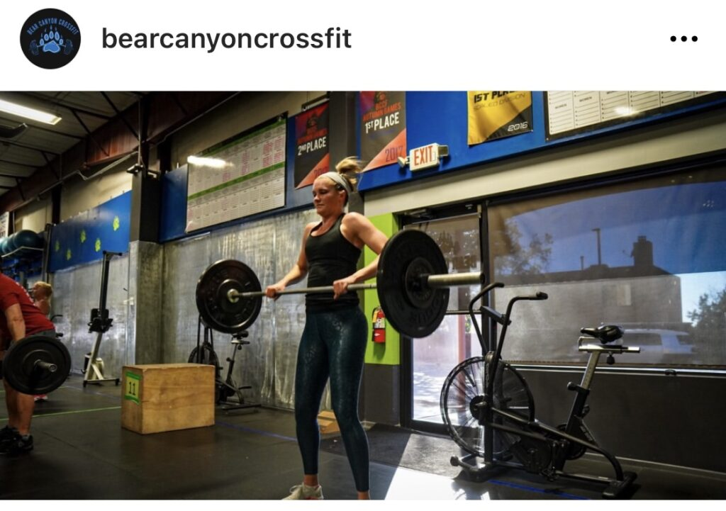 a blonde woman in a gym lifting weights