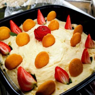 Freshella Catering banana mousse garnished with sliced strawberries and vanilla wafers