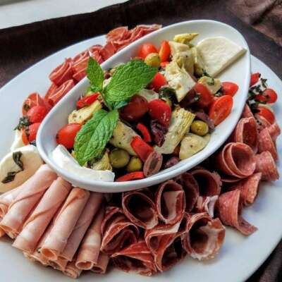 Assortment of meats and cheeses. Olives, artichokes, and red peppers