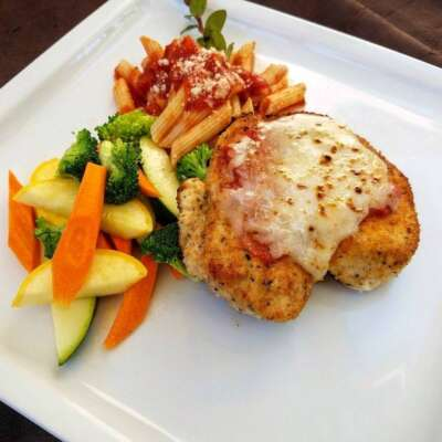 Chicken parmesan with side of pasta and vegetables