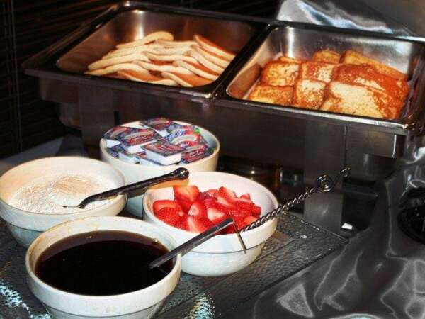 French toast bar with texas toast, strawberries, powdered sugar, and syrup