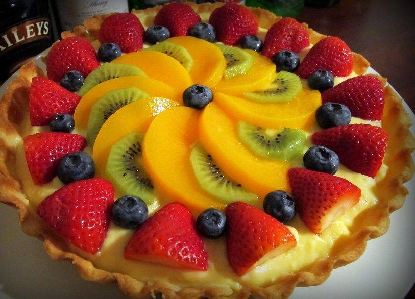 Fruit tart with slices of kiwis, berries, and peaches