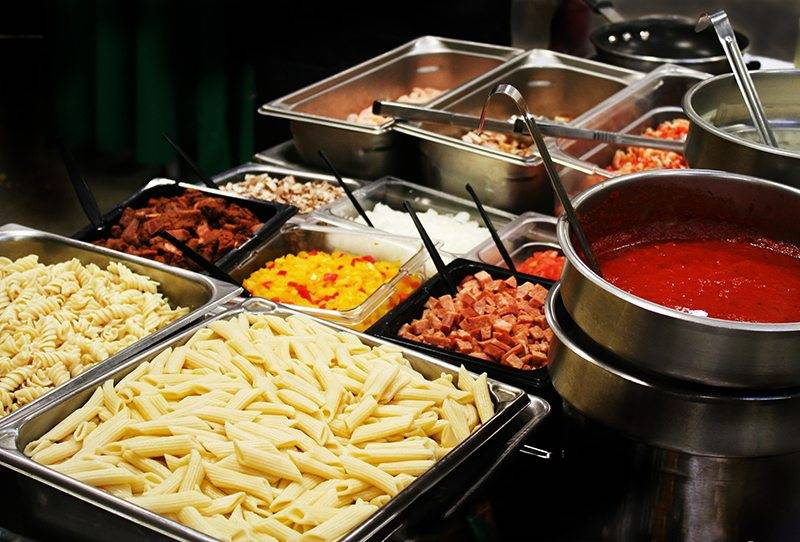 Pasta bar with variety of pasta, meats, and sauces