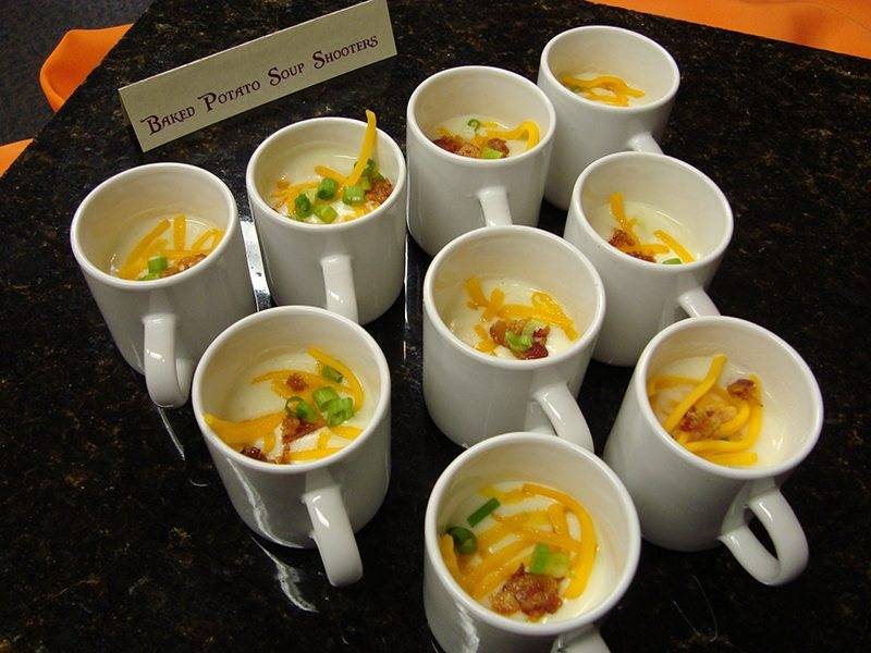 Potato soup, cheese, bacon, and chives in a mini mug