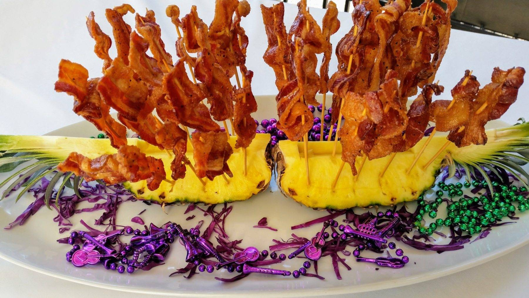 Candied bacon, on skewers, displayed on pineapple halves