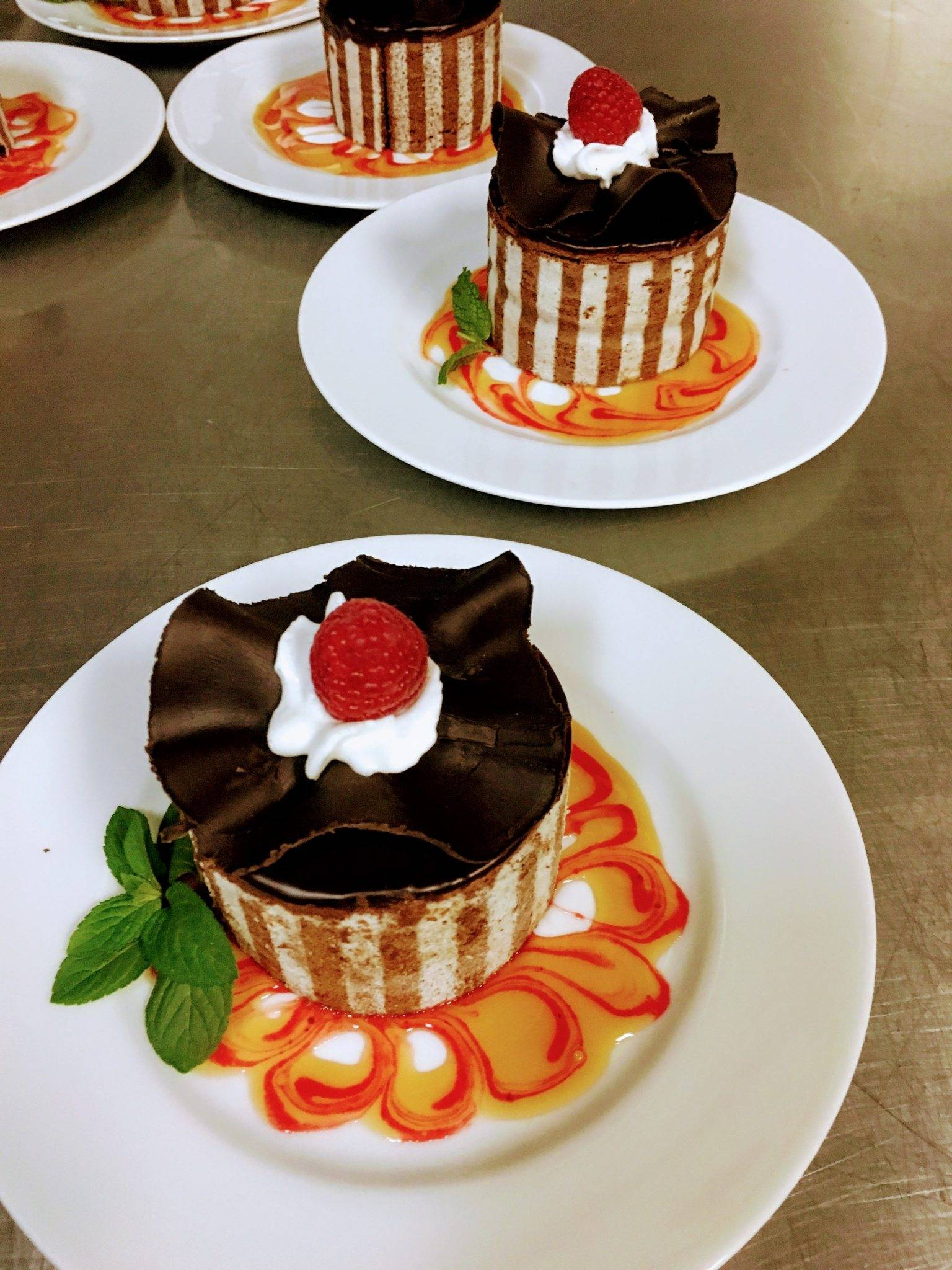 Personal chocolate cake topped with a raspberry and cream
