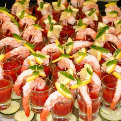 display of shrimp shooters, shot glasses with bloody mary mix topped with shrimp and lemon wedge garnish