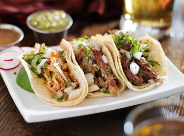 Catering street tacos, showing shredded chicken taco on corn tortilla and shredded beef taco on corn tortilla garnished with cilantro and diced onions