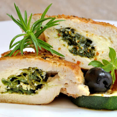 Plate with sliced chicken stuffed with spinach and mozarella