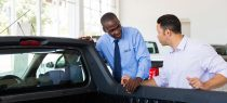 man with salesman after selling his used truck