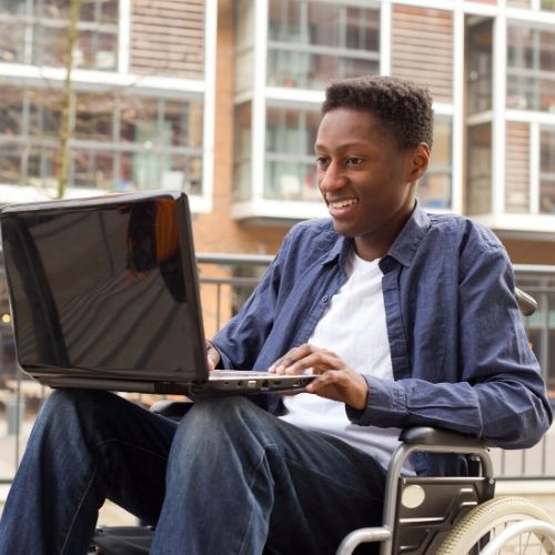 Black man in a Wheelchair using a computer