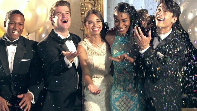 A group of five multi-ethnic young men and women, 17 to 19 years old, at prom. The two teenage girls are wearing prom dresses and the boys are wearing tuxedos. They are standing together, laughing and are showered with confetti.