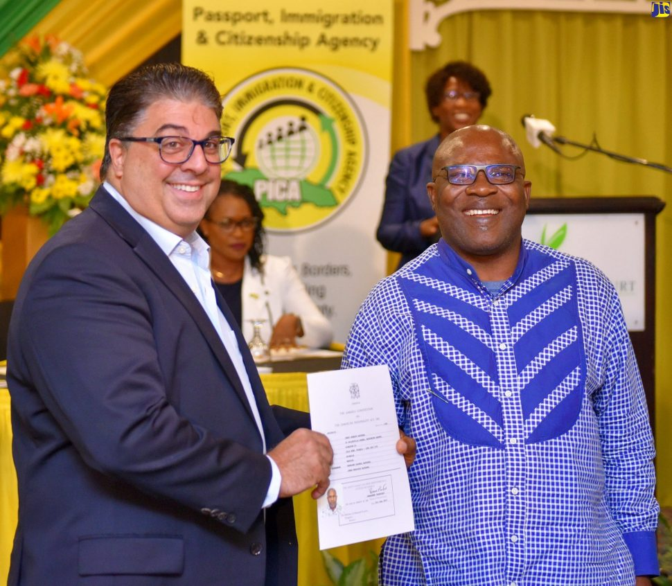 Passport, Immigration and Citizenship Agency (PICA) Advisory Board Chairman, Joseph Issa (left), presents Jerry Bayeshea with his citizenship certificate. The presentation was made during PICA's fourth citizenship swearing-in ceremony at The Knutsford Court Hotel in New Kingston, on Thursday (June 27).