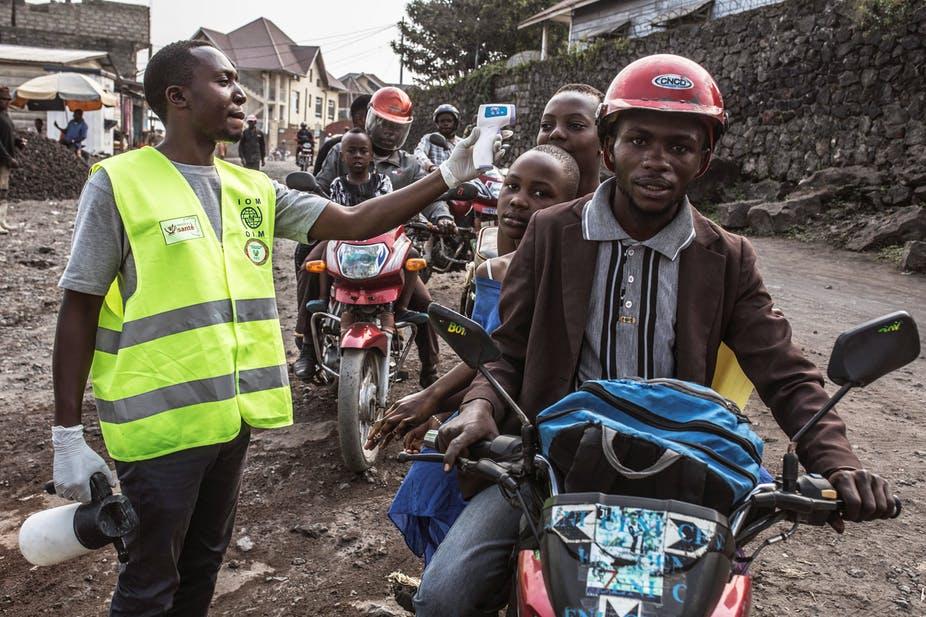 A worker of the Democratic Republic of Congo Health Ministry checks people's temperature in Goma