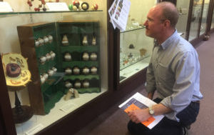Jim Cullen kneeling in front of a display case of teeth moulds at a museum