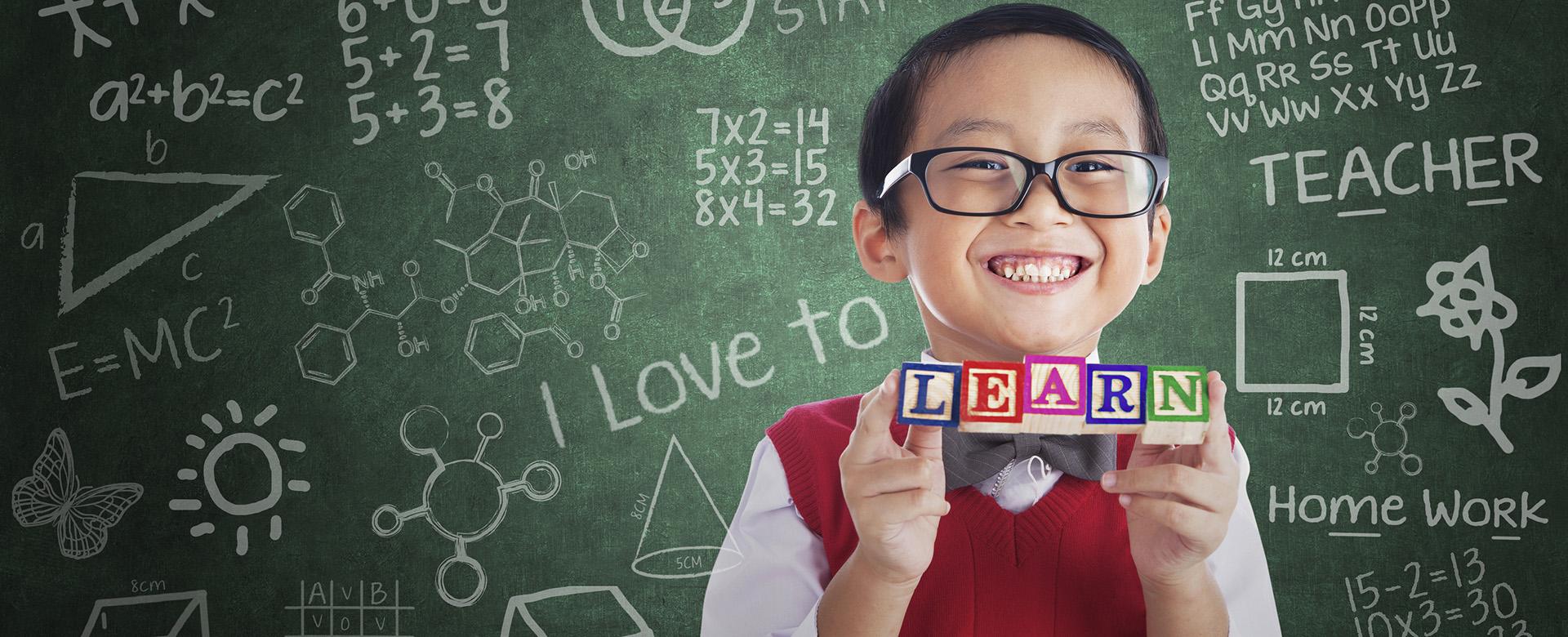 Portrait of asian elementary school student showing LEARN word in class