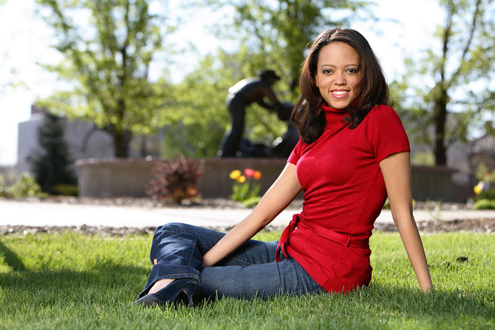 A female high school student sits on the campus of an HBCU while participating in a series of campus tours.